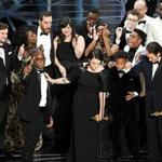 Producer Adele Romanski (center) with writer/director Barry Jenkins, and other cast and crew members accepted the best picture Oscar.
