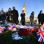 epa05868191 People stand by to look at flowers and Union jack flags placed on Parliament square by well-wishers in London, Britain, 24 March 2017. Well-wishers have flocked to the scene of the 22 March terror attack to pay their respects to those killed in the attack. Scotland Yard said on 24 March 2017 that police have made nine arrests in relation to the terror attack in the Westminster Palace grounds and on Westminster Bridge on 22 March 2017 leaving at least five people dead, including the attacker, and 29 people injured. EPA/ANDY RAIN