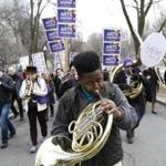 Boston, MA - 3/28/2017 - Jordan Volel,12, a student from the Conservatory Lab Charter School plays his French horn as he marches to the State House during what organizers called an