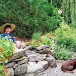 "Leslie Fillnow in her Camden, Maine, garden; 12-year-old English-style chocolate Labrador Tara relaxes in an area dubbed ""The Wetlands."""