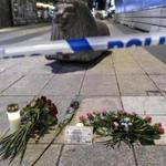 Candles and flowers are placed near the site where a beer truck crashed into a department store in central Stockholm, Sweden, Friday, April 7, 2017. The hijacked beer truck plowed into pedestrians at the central Stockholm department store on Friday, sending screaming shoppers fleeing in panic in what Sweden's prime minister called a terrorist attack. (Maja Suslin/TT NEWS AGENCY via AP)