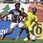 New England Revolution midfielder Xavier Kouassi, left, and Columbus Crew midfielder Mohammed Abu, right, vie for control of the ball during the first half of an MLS soccer game, Sunday, May 21, 2017, in Foxborough, Mass. (AP Photo/Steven Senne)