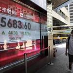 A man walked past an electronic board showing stock prices in Hong Kong on Monday. A rally led to three Chinese real-estate tycoons increasing their wealth by $5.4 billion.
