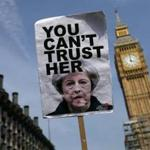 A protester carried a placard critical of Prime Minister Theresa May during demonstrations near Big Ben Wednesday.