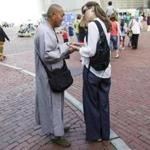 A man dressed in monk-like robes attempts to solicit money from passersby in exchange for beads or prayer cards.