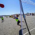 Ball and goalie are airborne at the Boston Beach Soccer Tournament Series at Nantasket Beach.
