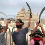 In front of a centerpiece display showing the USS Constitution, young pirates raised their swords at the Revere Beach International Sand Sculpting Festival in Revere on Saturday.