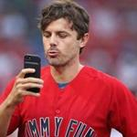 Casey Affleck checked his phone before throwing out the first pitch at Fenway Tuesday night.