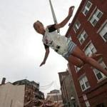 Boston, MA - 8/15/2017 - Ava Bonavita, 11, takes to the air as she is hoisted above North street in Boston's North End during a test run for the traditional
