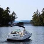 Stewart Woodworth at the helm of his boat as he looked for uncharted rocks on Winnipesaukee.