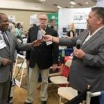 A man (left) received $300 in a cash giveaway at the Cape Cod Symposium on Addictive Disorders on Friday.