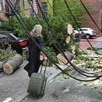 A woman with her luggage rolled past wires, cut trees, and debris Thursday.