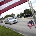 A hearse carrying the body of the US Army Sergeant La David Johnson drove away after Saturday's funeral service in Cooper City, Fla.