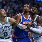 Boston, MA: 10-24-17: The Celtics Jayson Tatum (left, and Jaylen Brown (right) surround the Knicks Lance Thomas under the basket in second half action. (Jim Davis/Globe Staff)