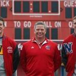 Eric Ramstrom is flanked by his sons Gus (left) and Tim at Memorial Field in Natick. The three wrestled and played football for Natick High.