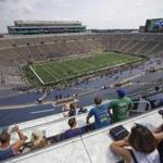 In this Sunday, Aug. 20, 2017 photo, fans take in views from the Duncan Student Center during open tours of Notre Dame Stadium during the New & Gold scrimmage game in South Bend, Ind. University officials offered the public on Sunday the chance to tour portions of the new buildings that now hug the stadium on three sides. The public also was invited to watch a scrimmage in the stadium, which features some new amenities, including a huge video board on the south end, attached to the new O'Neill Hall. (Michael Caterina/South Bend Tribune via AP)