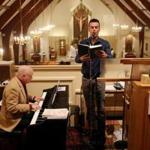 Andrew Giordano sings during a service at St. Barbara Parish Church in Woburn accompanied by Todd Theriault.