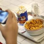 A woman takes a picture of her breakfast at Kellogg's Cafe NYC in New York, Thursday, Dec. 14, 2017. Kellogg hopes the new store will be a place where millennials want to buy cereal by the bowl and then hang out. (AP Photo/Seth Wenig)