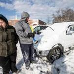 01/05/2018 GLOUCESTER, MA Katerina Kariores (cq) (left) and her boyfriend Mike Paul (cq) survey the damage on their two cars with water damage in a parking lot that flooded during yesterday's blizzard at Gloucester High School. (Aram Boghosian for The Boston Globe)