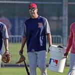 Fort Myers, FL 2/21/2018: Former Red Sox 3B and World Series MVP Mike Lowell (center) helps carry a bucket of baseballs in from a practice field session. It was the final day of workouts at Spring Training for the Red Sox today at the Player Development Complex at Jet Blue Park. The team begins exhibition games with a doubleheader vs college teams tomorrow. (Jim Davis/Globe Staff)