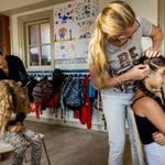 Parents combed children's hair to see if they are infested by head lice at a primary school in Scheveningen, Netherlands.