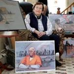 Jane Collins in her Duxbury home with some of her best-known courtroom drawings.