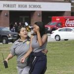 A student is comforted by a school official outside Forest High School.