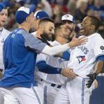 Toronto Blue Jays' Curtis Granderson welcomed by teammates after he hit a walk-off home run against the Boston Red Sox during the 10th inning of a baseball game Tuesday, April 24, 2018, in Toronto. Toronto won 4-3. (Fred Thornhill/The Canadian Press via AP)