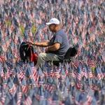 Boston, MA - 05/23/18 - Oscar Borraro (cq) rode his chair through a field of thousands of American flags. His father served in the army. Hundreds of volunteers planted flags in Boston Common for Memorial Day to honor the roughly 37,000 Massachusetts service personnel who have given their lives since the Revolutionary War. (Lane Turner/Globe Staff) Reporter: (in caps) Topic: (24flaggarden)