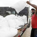 Travis Lee loaded sand bags onto a truck bed on Saturday in Gulfport, Miss.