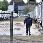 A Lawrence firefighter walked past a row of travel trailers Saturday.