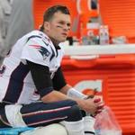 Tom Brady sits on the bench after getting pulled midway through the fourth quarter of last Sunday's loss to the Titans.