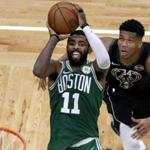 Boston Celtics guard Kyrie Irving (11) shoots against Milwaukee Bucks forward Giannis Antetokounmpo (34) in the fourth quarter of an NBA basketball game, Friday, Dec. 21, 2018, in Boston. The Bucks won 120-107. (AP Photo/Elise Amendola)