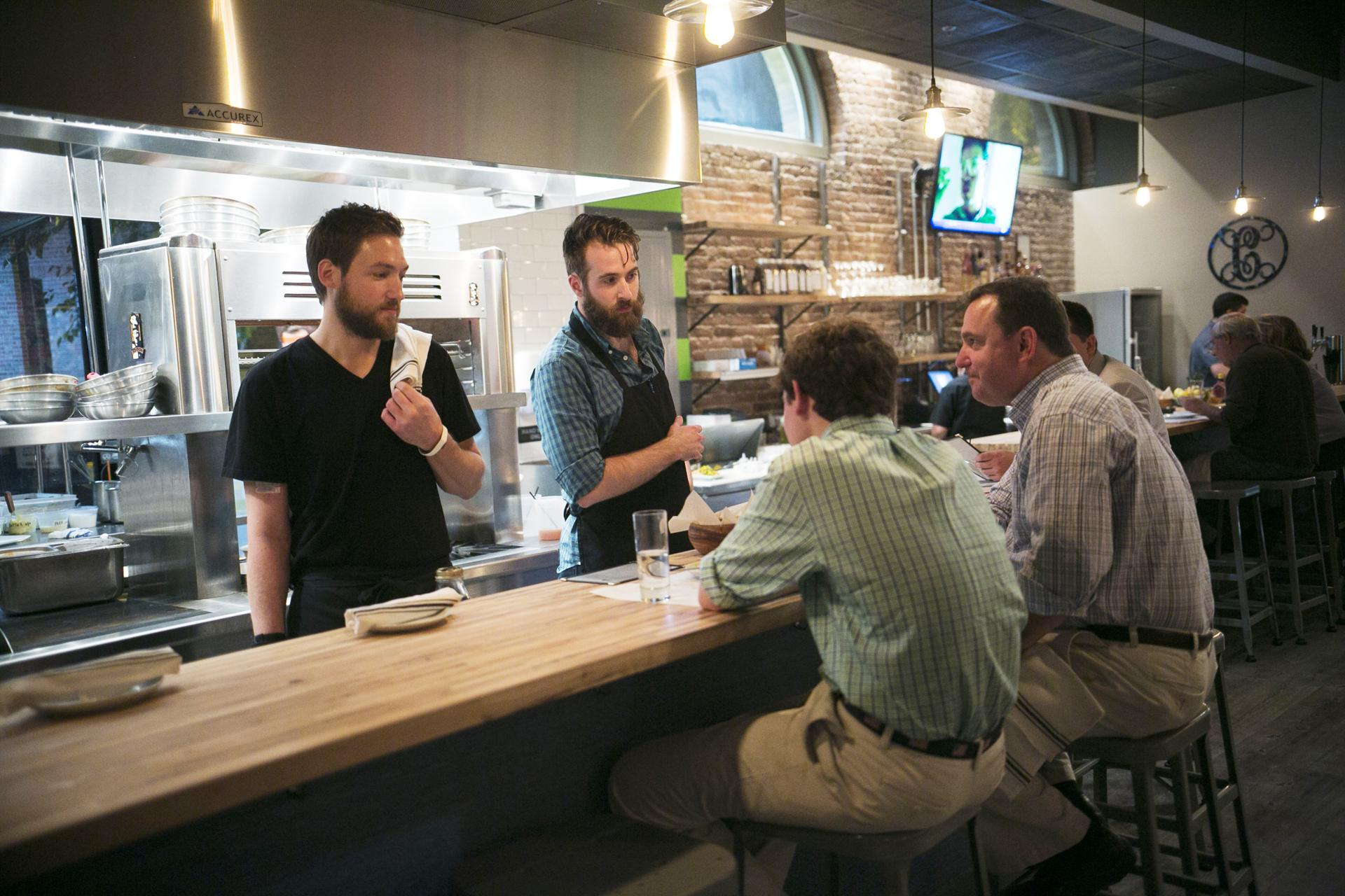 Michael Ryan Buckley (right) and Jacob White (left) co-owner and chef talk to the patrons at Comedor.
