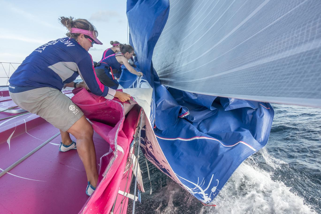January 19, 2015. Day 16 of Leg 3 to Sanya onboard Team SCA. Sally Barkow helps pull the J1 sail on board after the Team changes sails.