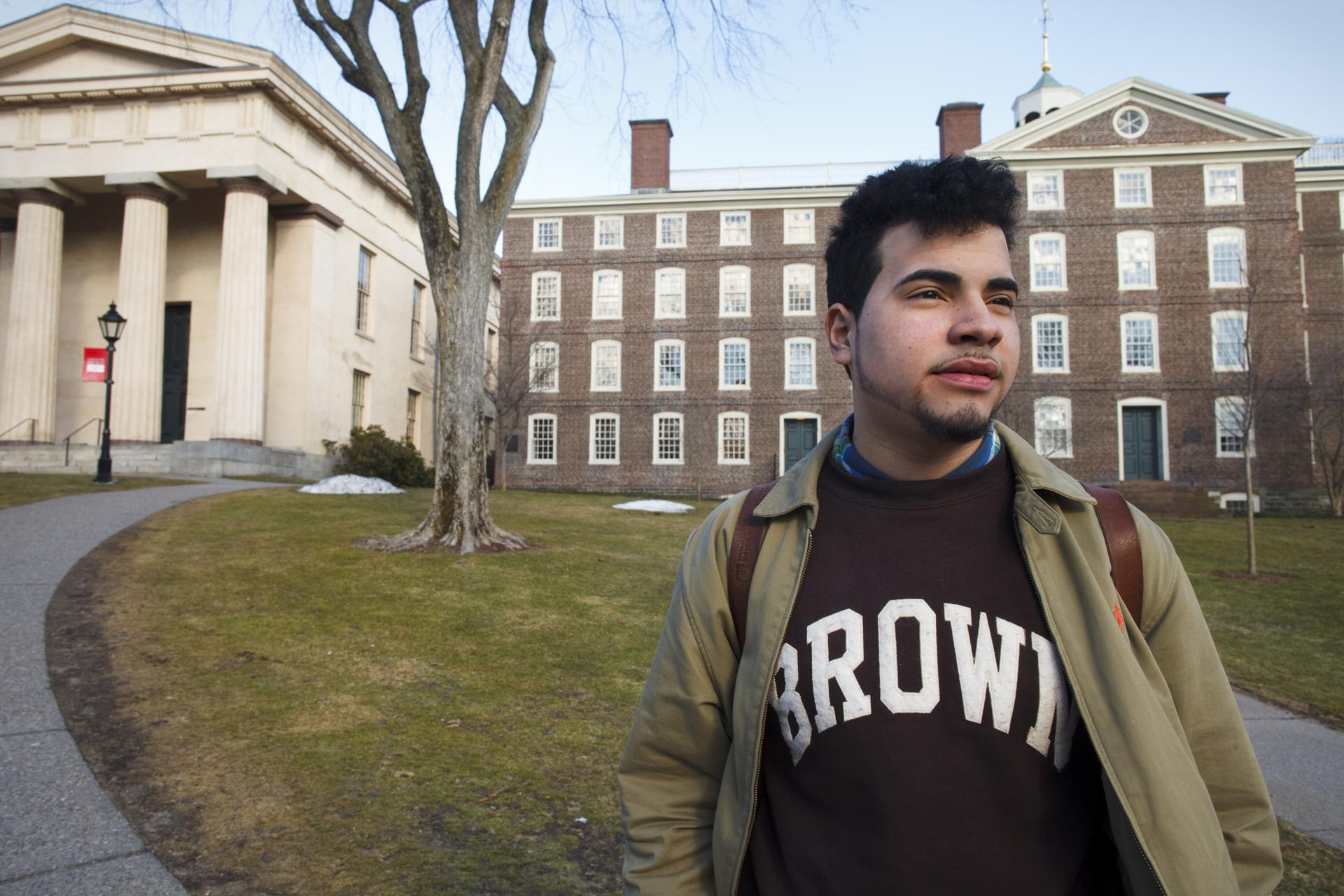 "03/17/2015 - Providence, RI - Alejandro Claudio, cq, a freshman at Brown University, walks through campus on a sunny Tuesday afternoon. Claudio gained a full-ride scholarship to the Ivy League school, which is the only way that the son of poor immigrant parents could hope to attend. He is shocked regularly by the huge contrast between his world at school and the world he's used to at home. Claudio is majoring in economics. ÒIf I fail, IÕm going back to poverty, to working in a factory,"" said Claudio. ""I need to get good grades and get a job that pays well enough to help feed my family,Ó added Claudio. Topic: 041215ivyleague. Photo by Dina Rudick/Globe Staff."