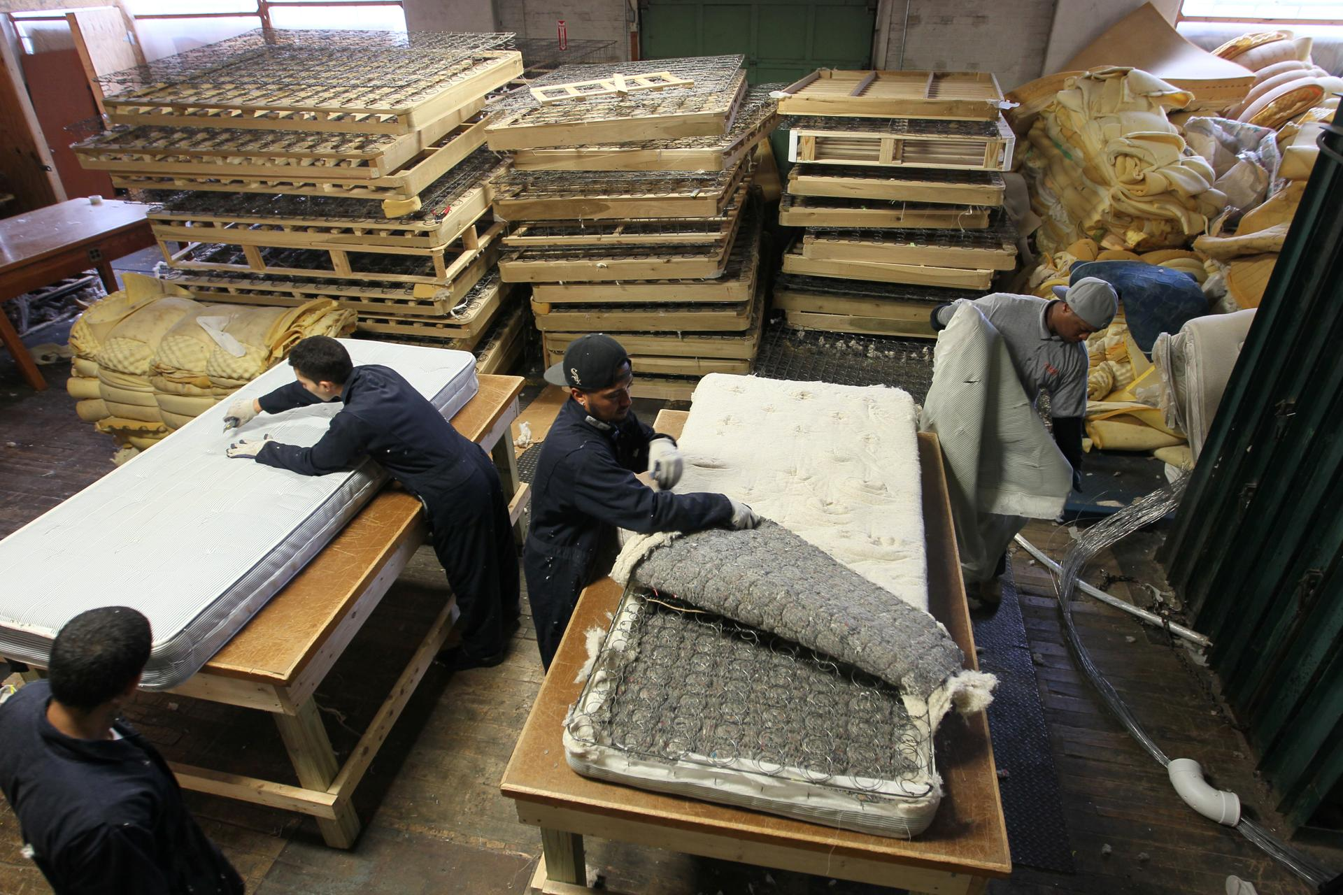 A worker in Lawrence began the process of taking apart a mattress for recycling.