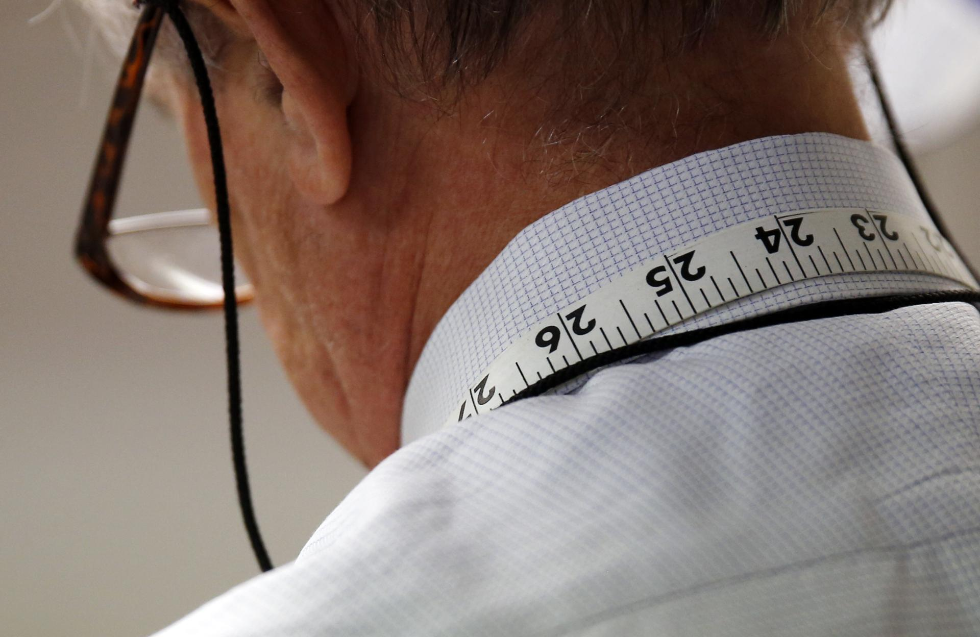 Measuring tape hangs around tailor Joe Calautti's neck as he worked on a suit jacket.