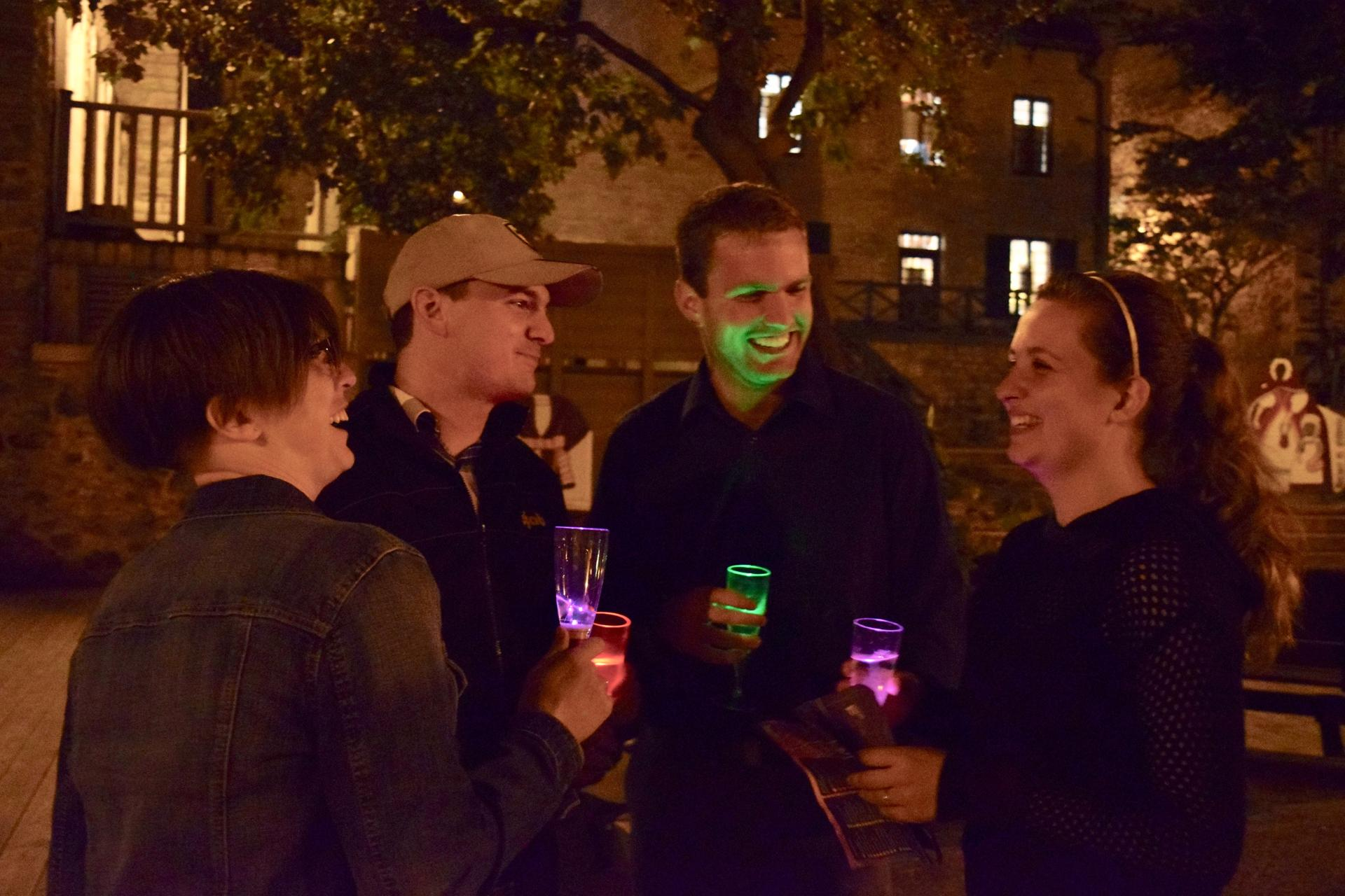 Groups drink from illuminated wine glasses during the Night of the Galleries on Sept. 16 in Quebec City. More than 35 art galleries participated in the event. Attendees could hop from gallery to gallery and fill their wine glasses along the way.