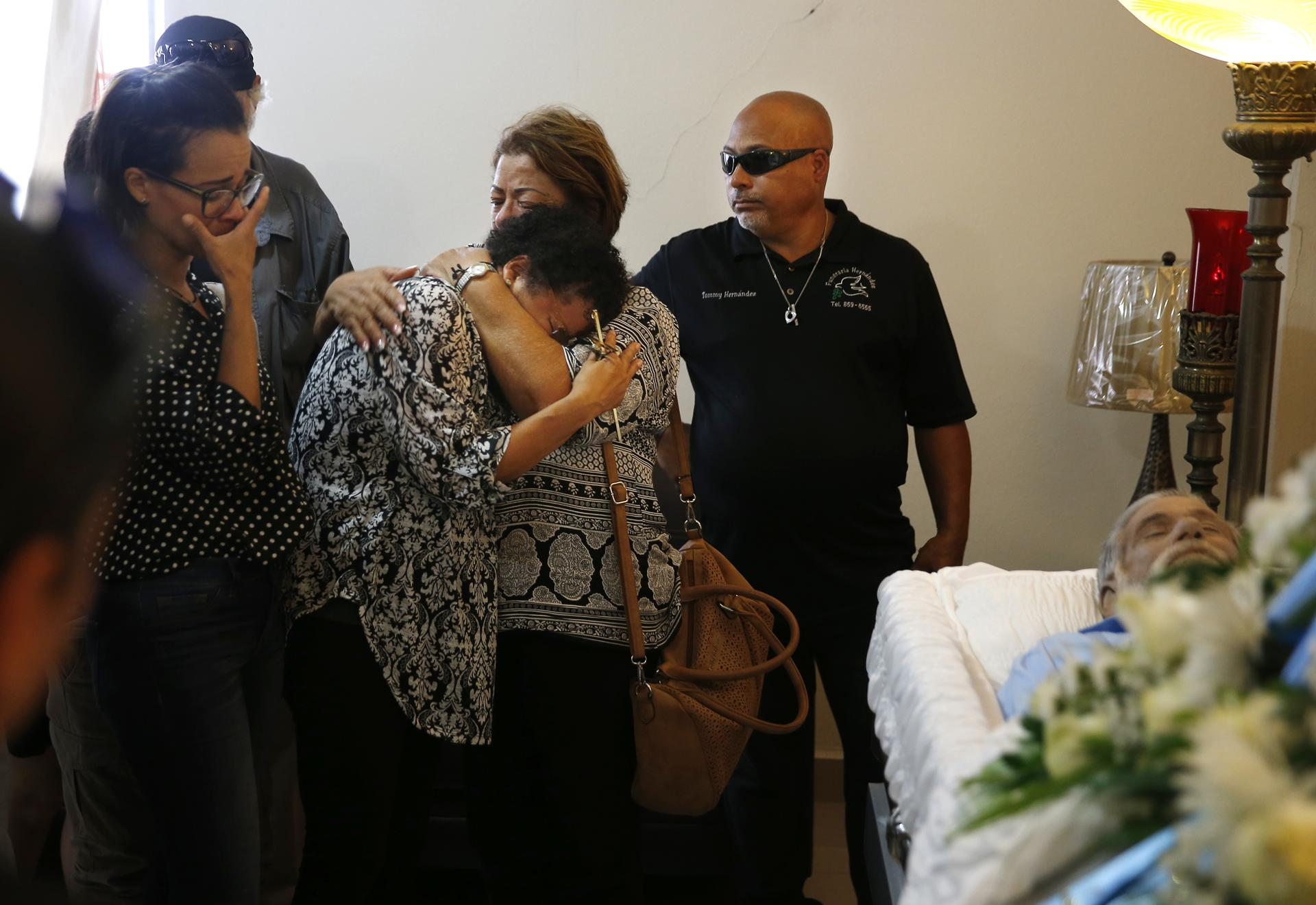 Ana Ruiz was consoled as funeral directors prepared to close the casket of her husband, Victor Hugo Ruiz, in Corozal, Puerto Rico.