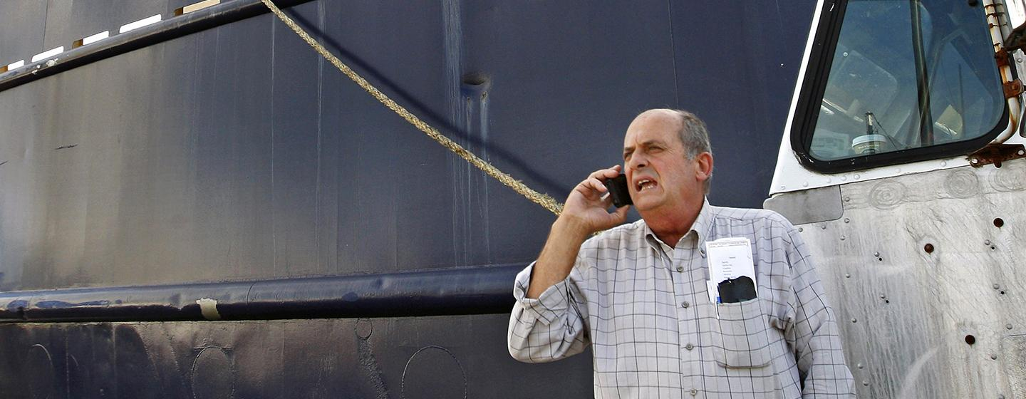 Carlos Rafael talked on the phone at Homer's Wharf in New Bedford near his herring boat F/V Voyager.