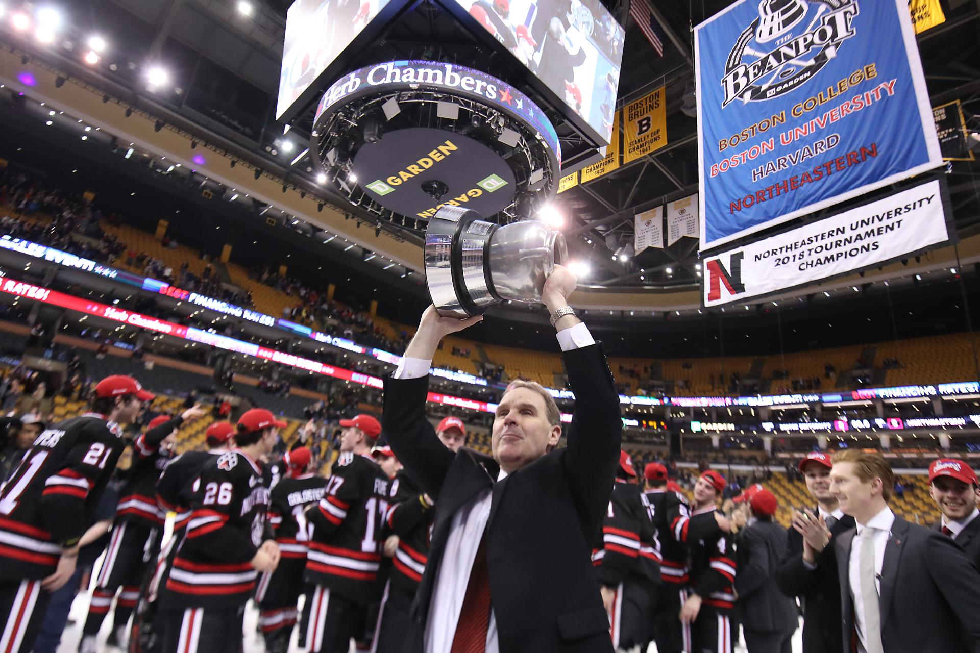 Northeastern University head coach Jim Madigan held up the Beanpot trophy after they defeated Boston University.