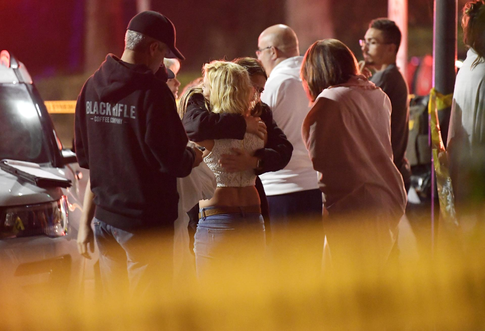 People comfort each other as they stand near the scene Thursday, Nov. 8, 2018, in Thousand Oaks, Calif. where a gunman opened fire Wednesday inside a country dance bar crowded with hundreds of people on