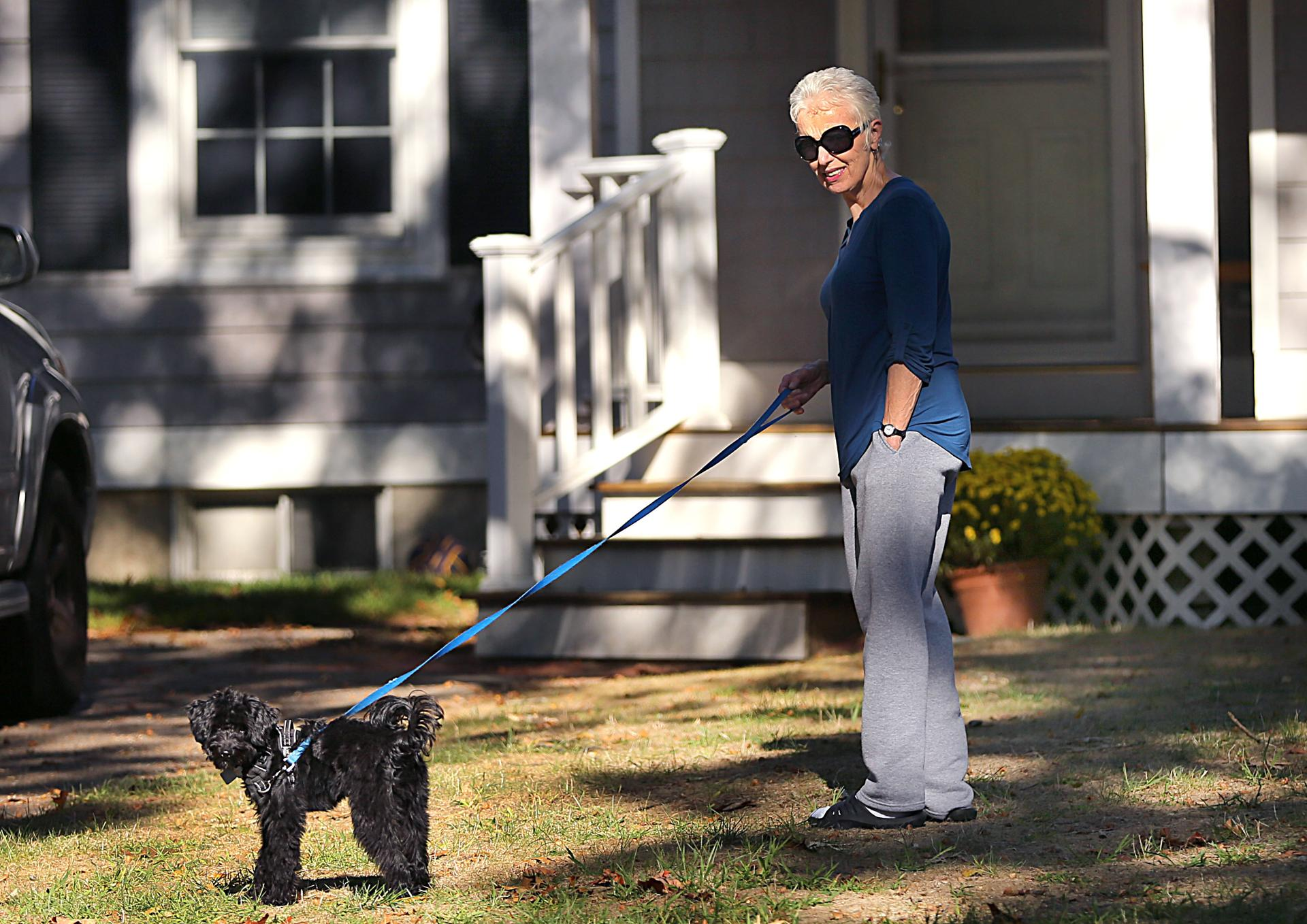 Hingham 09/25/19-FOR PUBLICATION ONLY WITH SHELLEY MURPHY STORY The former longtime girlfriend of mobster Whitey Bulger, Catherine Greig walks her dog on the front lawn of the home she is staying at in Hingham which is the residence of one of Billy Bulger's daughters. Photo by John Tlumacki/Globe Staff(metro)