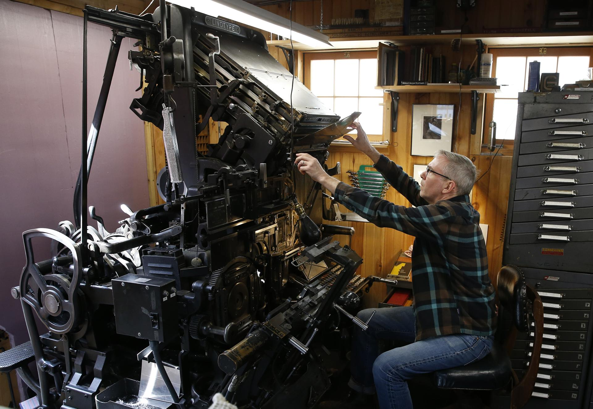 In his Jamaica Plain workshop, Michael Babcock demonstrated a 75-year-old Linotype Model 31, maybe the last hot-type press in Boston. Linotypes revolutionized the newspaper industry.