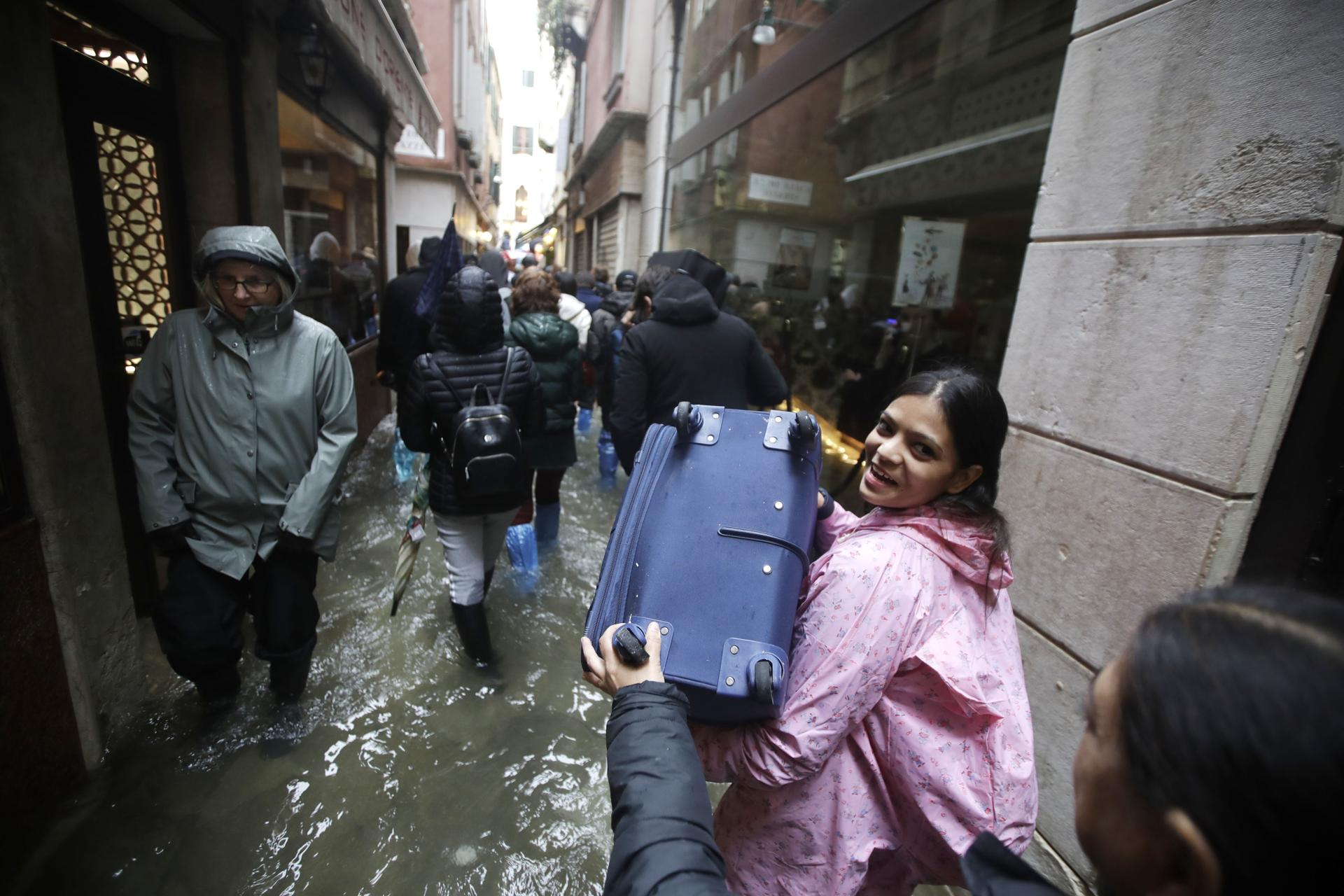 Tourists carried luggage through a flooded Venice, Italy, during high tide.