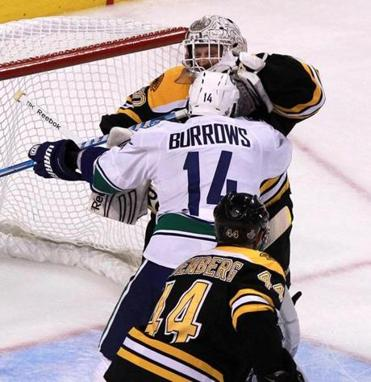 Bruins goalie Tim Thomas tangles with Vancouver's Alex Burrows in the third period.