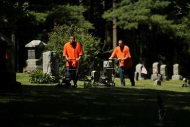 Christian Roche (left) and Jose Rivera from MCI-Shirley cut grass at a cemetery during a work-crew assignment during the summer.