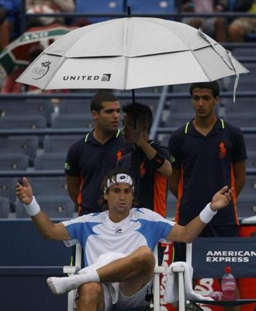 David Ferrer of reacts as rain delays his match with Andy Roddick.