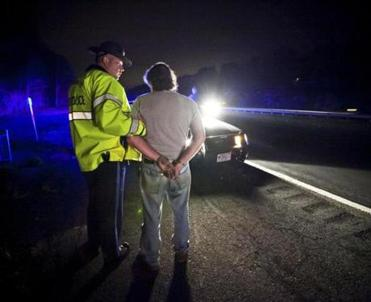 "State Police Trooper Matthew Sheehan arrests a suspected drunken driver along Interstate 93. A breath test later indicates the driver's blood alcohol content is .17. Sheehan is on ""saturation patrol"" looking for drunken drivers before a state police sobriety checkpoint in Everett later in the night. (Aram Boghosian for The Boston Globe)"
